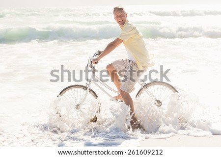 Happy man on a bike ride at the beach - stock photo