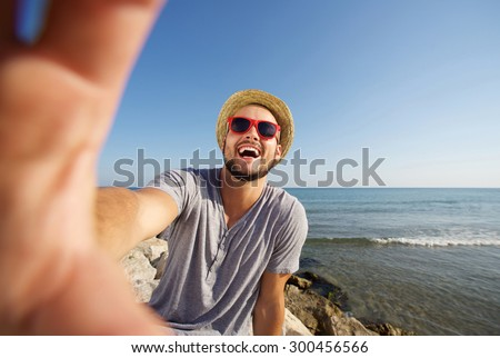 Happy man on vacation laughing at the beach taking selfie - stock photo