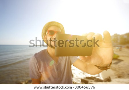 Happy man on vacation taking a selfie at the beach - stock photo
