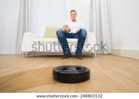 Happy Man Operating Robotic Vacuum Cleaner With Remote Control At Home - stock photo