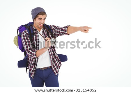 Happy man pointing while holding camera against white background - stock photo
