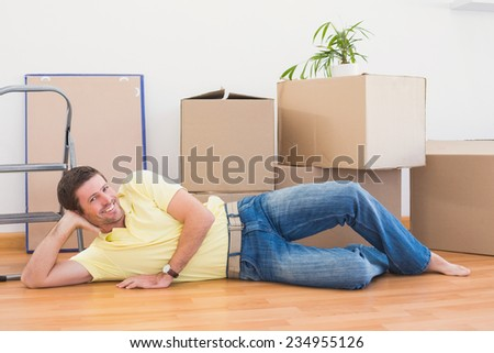 Happy man posing with moving boxes at home in the living room