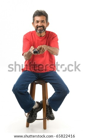 Happy man Pressing a button of the remote control . - stock photo