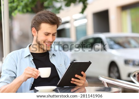 Happy man reading an ebook or tablet in a coffee shop terrace holding a cup of tea - stock photo
