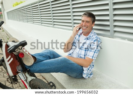 Happy man resting after a bike riding and talking the phone - stock photo