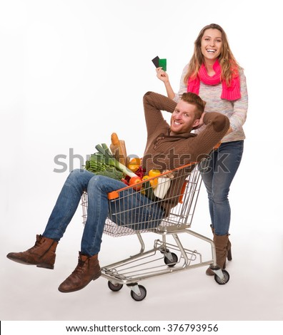 Happy man resting in shopping cart among fruits and vegetables over white background. Pretty lady pushing shopping trolley. - stock photo