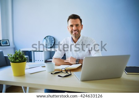 Happy man running small business from his home office looking at camera with laptop , glasses and notepad on desk - stock photo