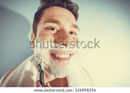 Happy man shaving using razor with cream foam. Handsome guy removing face beard hair. Skin care and hygiene. Instagram filter.