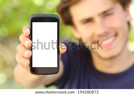 Happy man showing a blank mobile phone screen outdoor with a green background             - stock photo