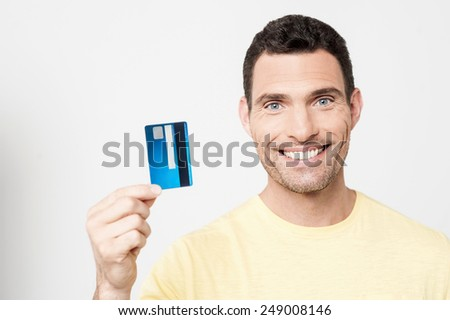 Happy man showing his credit card to camera - stock photo