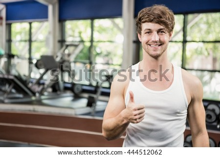 Happy man showing his thumbs up while exercising at gym - stock photo