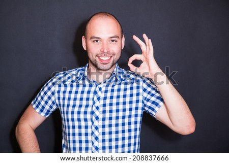 happy man shows OK against the black background - stock photo