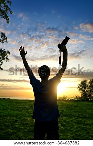 Happy Man Silhouette with Photo Camera on the Sunset Background - stock photo