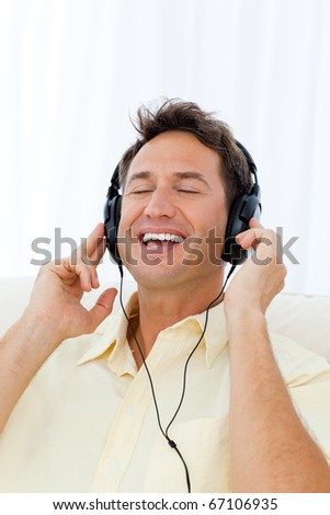 Happy man singing while listening to the music on the sofa at home - stock photo