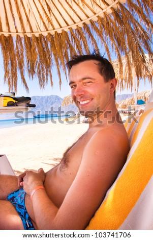 Happy man sits on a deck chair under a beach umbrella. Egypt. - stock photo