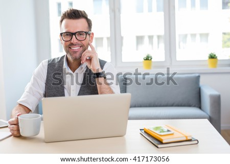 Happy man sitting at desk working with laptop from home - stock photo