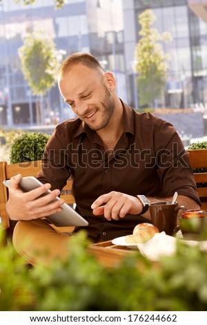 Happy man sitting on a bench outdoors, reading e-book, smiling. - stock photo