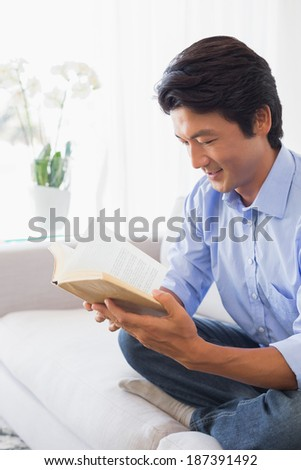 Happy man sitting on couch reading at home in the living room