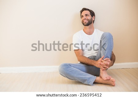 Happy man sitting on floor in his new home - stock photo
