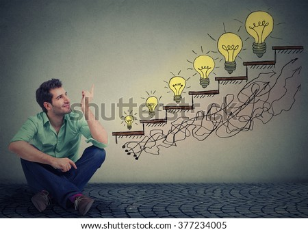 Happy man sitting on floor in his office pointing at business education success, promotion, company growth isolated gray wall texture background. Handsome guy looking up at growing up light bulbs