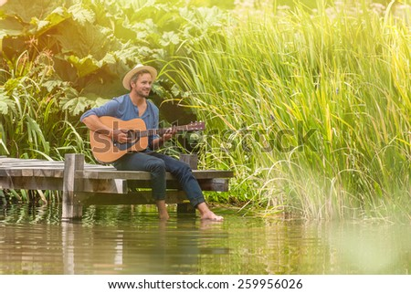 happy man sitting on the edge of a pontoon, feet in the water and playing guitar, he wears a straw hat - stock photo