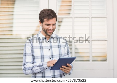 Happy man smiling at camera holding tablet on a sunny day - stock photo