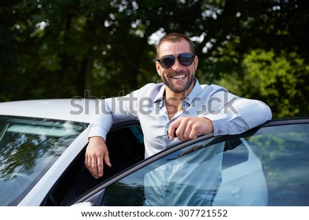 Happy man standing and leaning on car door