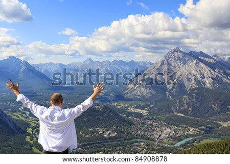 Happy man standing and looking at a panorama of Banff town and Bow river valley (Banff National Park. Alberta. Canada)