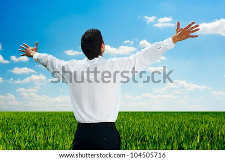 happy man standing at the field at sunny day - stock photo