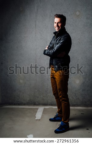 Happy man standing in underground garage wearing leather jacket with crossed arms