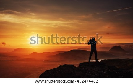 Happy man standing on a cliff at sunset.