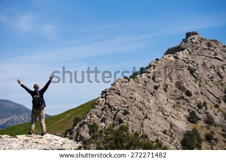 Happy man standing on the top of mount with his arms raised to the sky. - stock photo