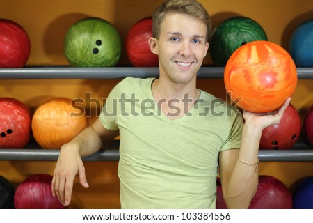 Happy man stands near shelves with balls and holds orange ball in bowling club; shallow depth of field - stock photo