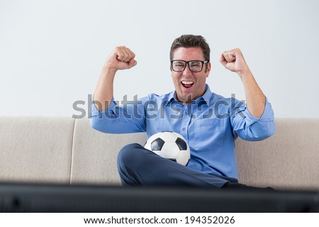 Happy man supporting his favorite soccer team at home - stock photo