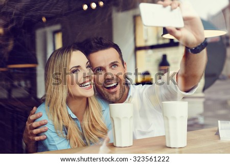 Happy man taking selfie with friend at cafe - stock photo