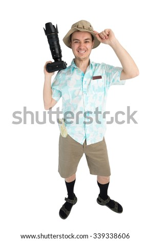 Happy man tourist in blue shirt, brown shorts and hat holds dslr camera. Traveler smiles and going to photo tour. Isolated on white background. Interesting trip on summer vacation.