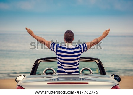 Happy man travel by car to the sea. Person having fun in cabriolet. Summer vacation concept
