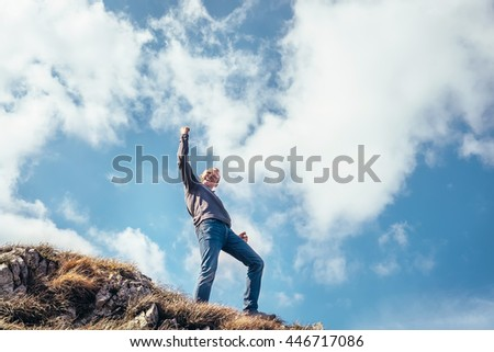 Happy man triumph his climb on the top of mountain