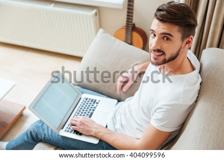 Happy man using laptop computer on the sofa at home - stock photo