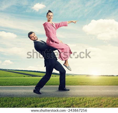 happy man walking on the road, carrying smiling woman. young woman sitting on man and pointing at the way