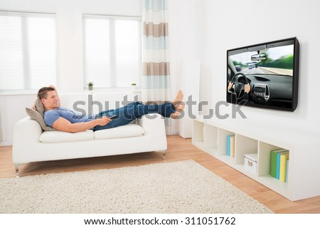 Happy Man Watching Movie While Lying On Sofa At Home - stock photo