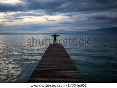 Happy man waving hands on an empty pier - stock photo