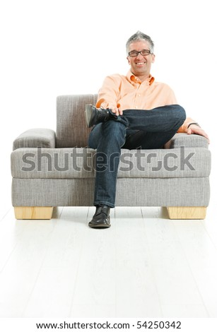 Happy man wearing jeans and orange shirt sitting on couch, talking on mobile phone. Isolated on white. - stock photo