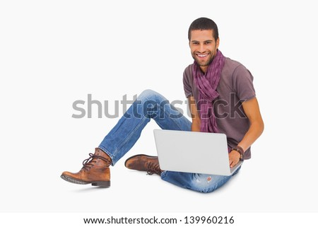 Happy man wearing scarf sitting on floor using laptop on white background