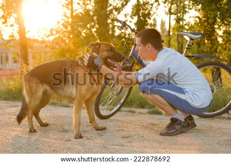 happy man with a dog in the park after a joint training - stock photo