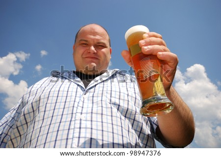 happy man with a glass of beer in front of blue cloudy sky - stock photo