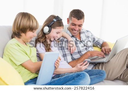 Happy man with children using technologies while sitting on sofa at home - stock photo