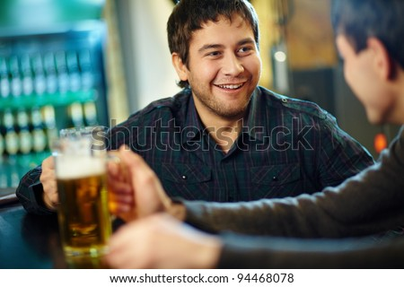 Happy man with glass of beer looking at his friend in pub