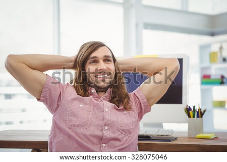 Happy man with hands behind head relaxing at computer desk in office