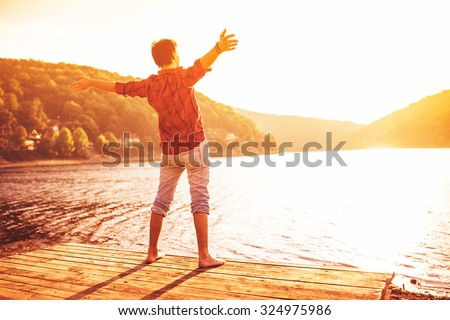 Happy man with hands up on sunset. Open arms, standing on a pier barefoot. Enjoying sun. Gazing sun.  Lens flare. - stock photo